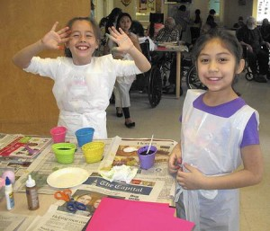 Christina Morales and Nina Barillas show off colorful fingers after dying eggs at the South River Health & Rehabilitation Center.