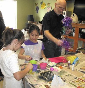 Christina Morales and Nina Barillas finish dying eggs while Jim Miller, president of the Kin-nect Board of Directors, supplies filling for their next project, Easter baskets.